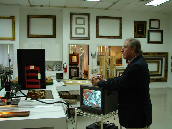 Gordon A. Lewis, Jr., founder and director of The Fine Arts Conservancy with their electric microscopy machine.